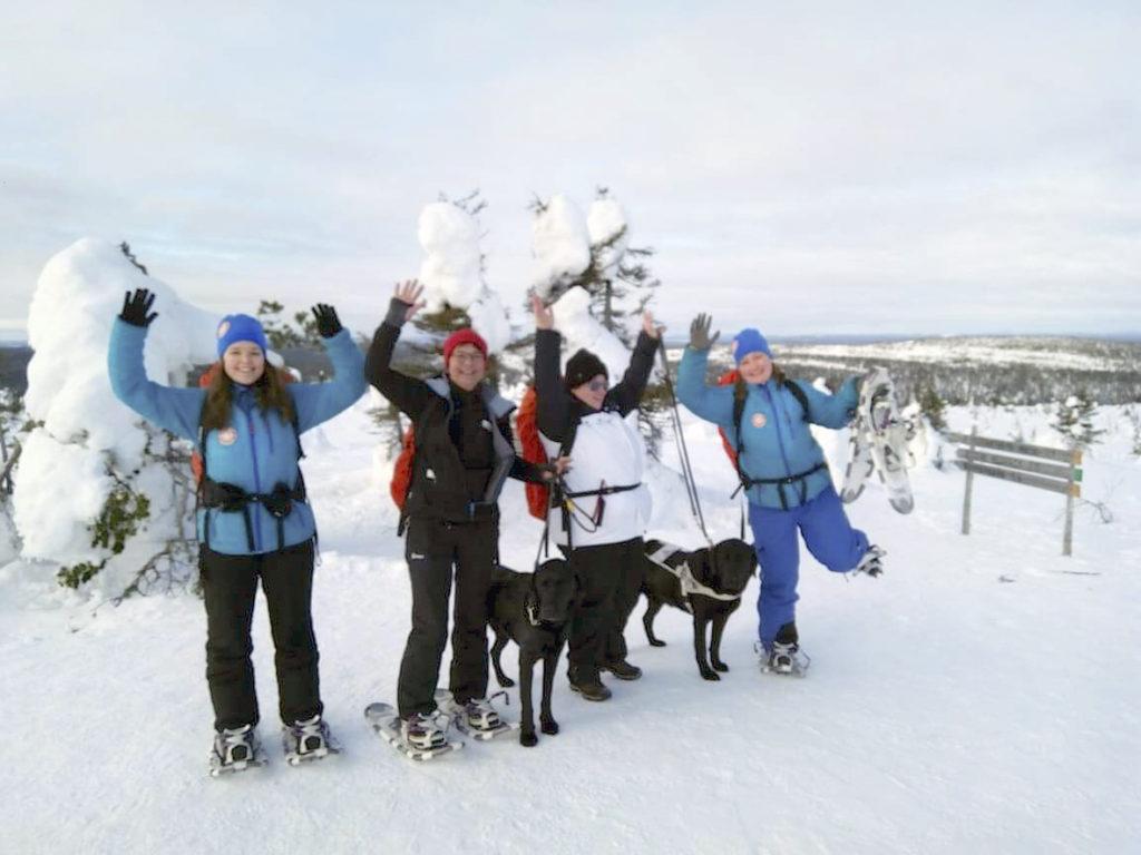 Ryhmätuuletus Riisitunturin huipulla! Me teimme sen! Taustalla huikeaa vaaramaisemaa ja lumen peittämiä matalia puita.