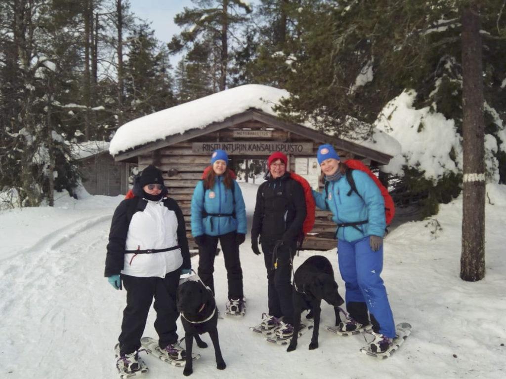 Heidi sekä Otto-koira, Miina, Sirpa Turo-koiran kanssa sekä Seikkailuapinoiden Heidi Riisitunturin kansallispuiston portilla lumikengät jalassa valmiina lähtöön.