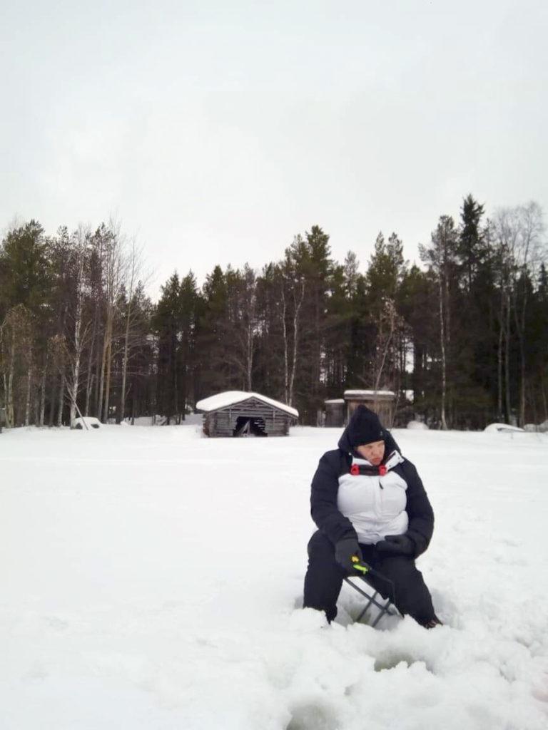 Odotellaan...odotellaan....odotellaan... Pitkä on pilkkijän aika. Ei syö kala, ei. Heidi istumassa pilkkijakkaralla lumen peittämällä järvellä.