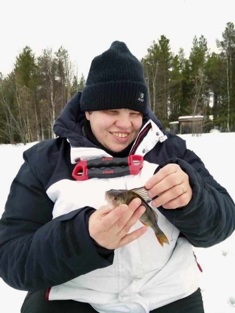 No tulihan sitä kalaa sittenkin -vaikkakin Sirpan pilkillä. Heidi tutkimassa pikkuisen ahvenen selkäevää hymy huulillaan.