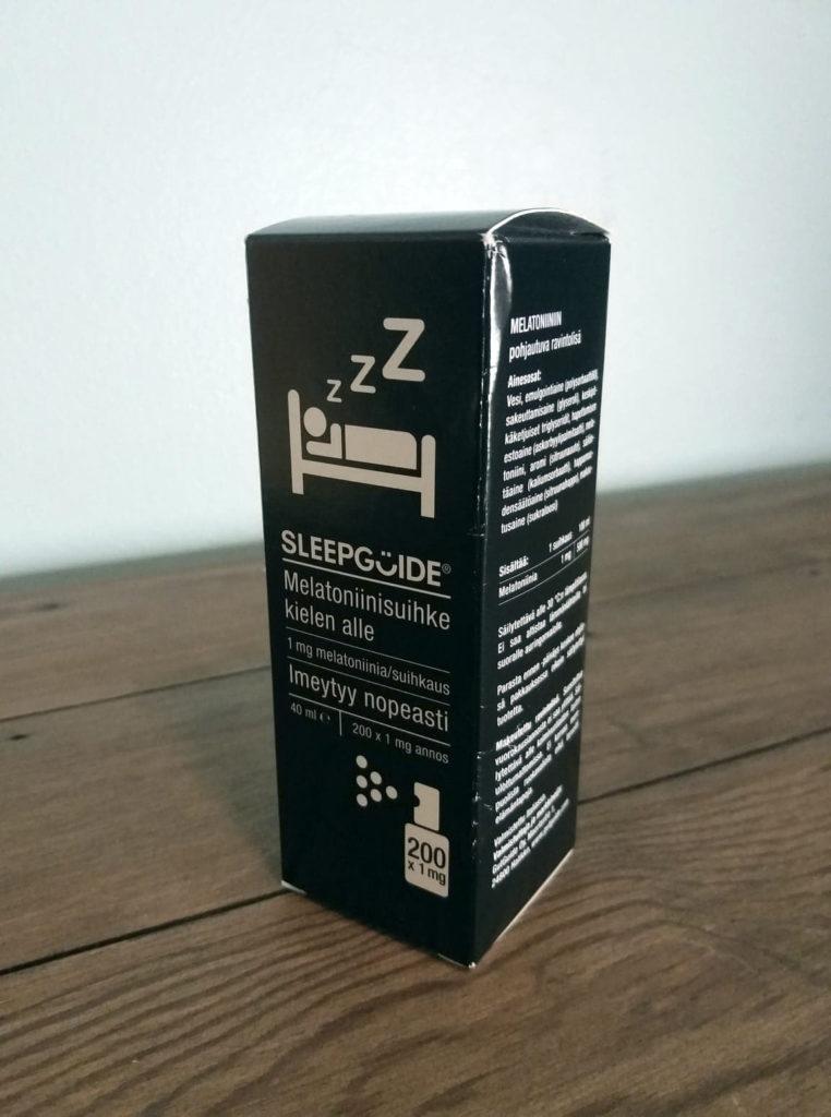 Sleepguiden nopeasti imeytyvä ja tehokkaaksi kehuttu melatoniinisuihke mustassa pahvipakkauksessaan puisen senkin päällä.