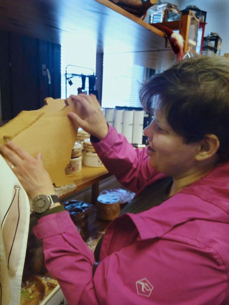 Heidi tunnustelee karhun muotoista puista pullotelinettä Ingan tuvan myymälässä.