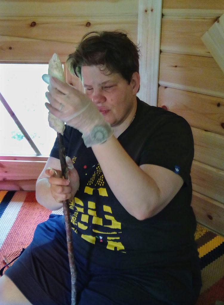 Heidi asettelee taikinaa pitkän puukepin päähän kodan lämmössä.
