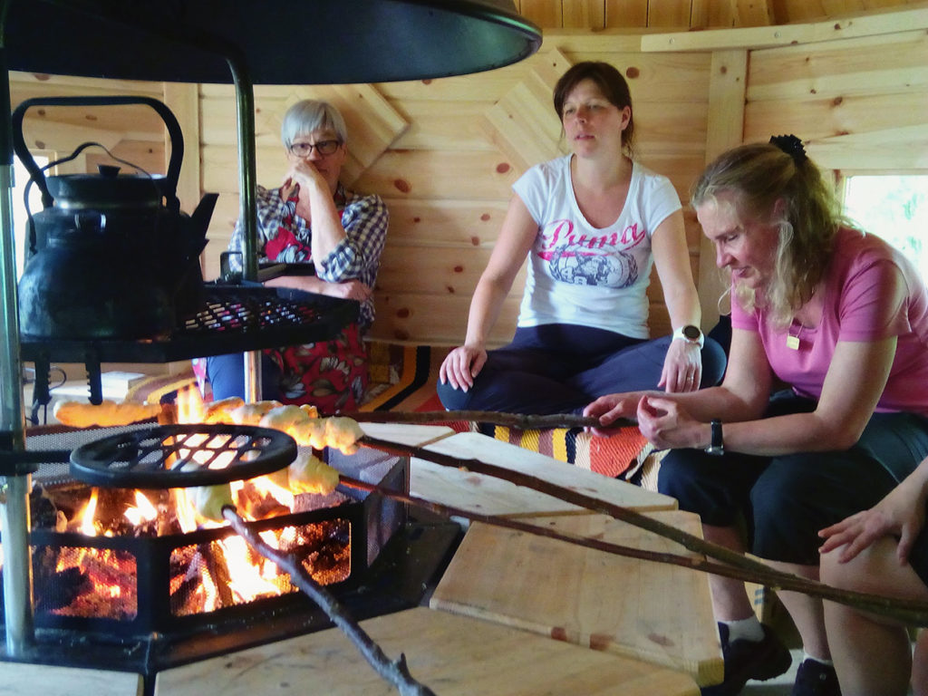 Retkeilijät rentoutumassa kodassa tulen lämmössä. Tikkupullat paistuvat ja vesi lämpenee nokipannussa tulen yllä.