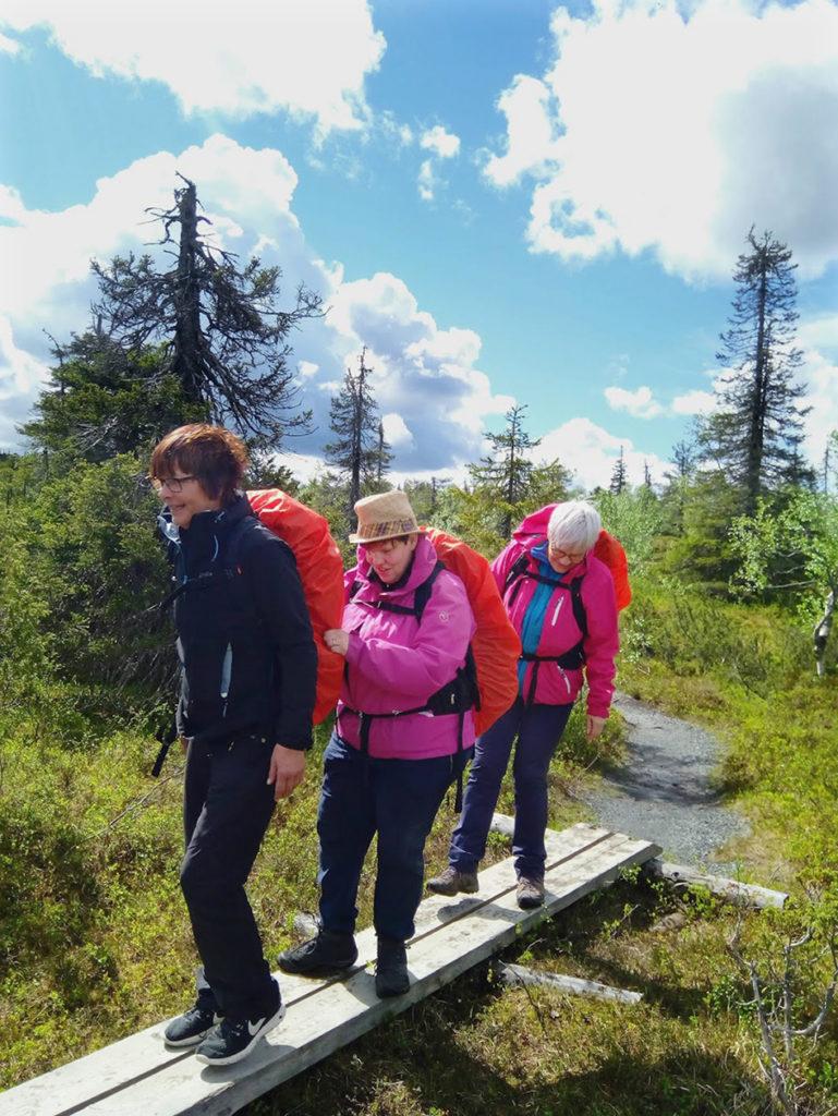 Lähdössä pitkoksia kulkemaan. Heidillä hyvä ote Sirpan rinkasta varmistaa turvallisen kulkemisen.  Aurinko paistaa kauniisti suurten pilvien välistä, ympärillä matalakasvuista harvaa havumetsää
