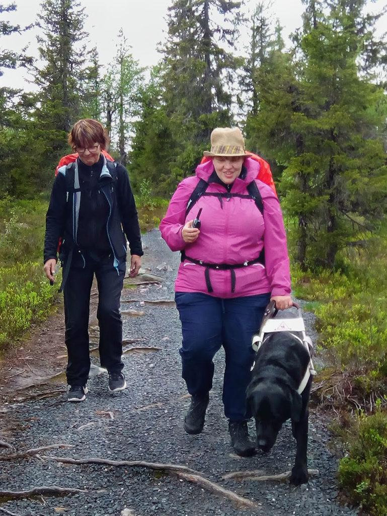Sirpa ja Heidi sekä Otto kulkemassa juurten raidoittamaa ja kivituhkan peittämää polkua sekä harjoittelemassa radiopuhelinten käyttöä. Heidiltä se näyttää sujuvan hyvin.