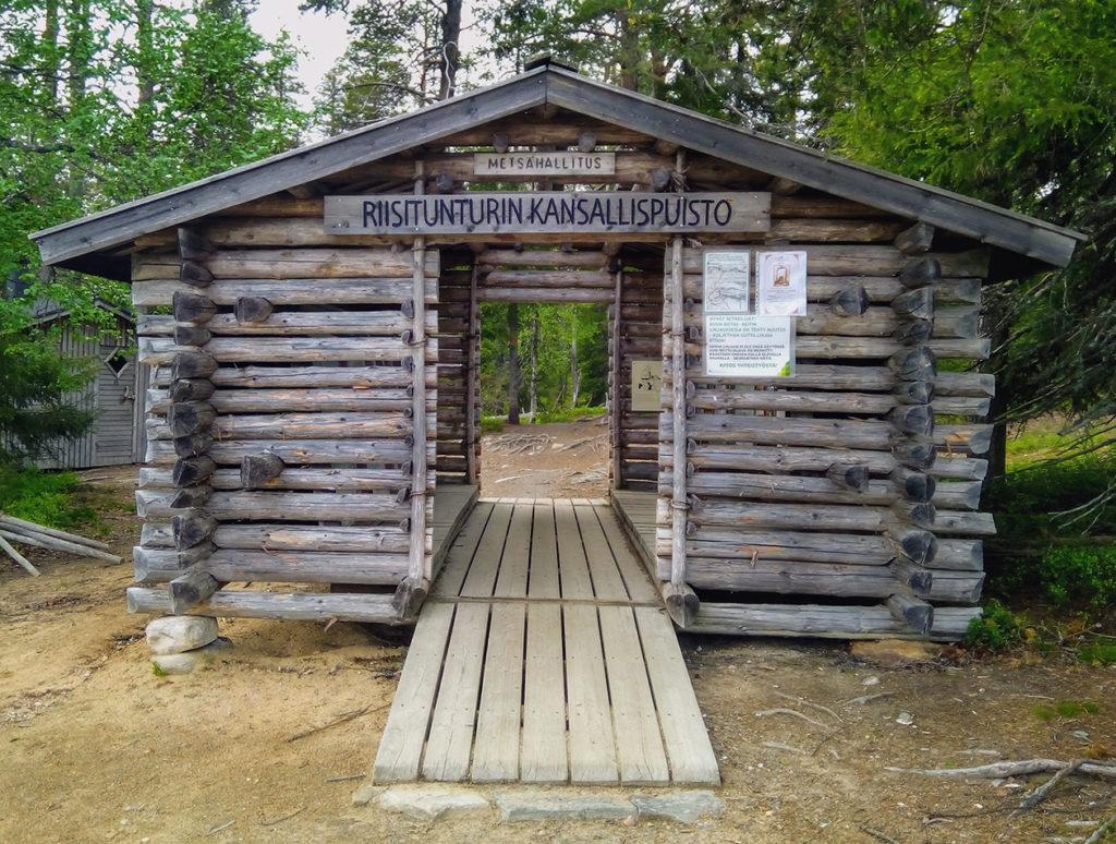 Sisäänkäynti Riisitunturin kansallispuistoon kulkee vanhan hirsistä tehdyn aitan läpi. Aitan päätyseiniin on tehty ovet ja aitan sisällä on infotauluja kansallispuistosta.