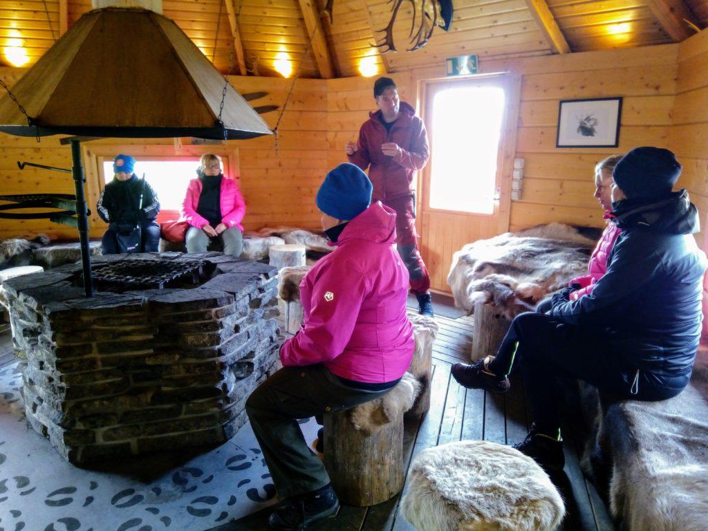 Kujalan porotilan isäntä Juha Kujala kertoo ryhmällemme poroista ja poron vuodesta istuessamme kodan lämmössä porontaljoilla.