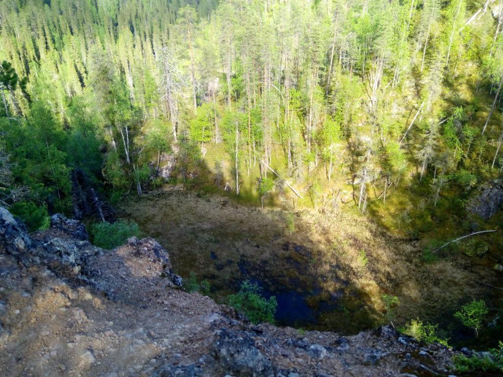 Huikaiseva näkymä pystysuoralta korkealta jyrkänteeltä alas laaksoon jossa suomaaston ympärillä kasvaa sankkaa metsää.