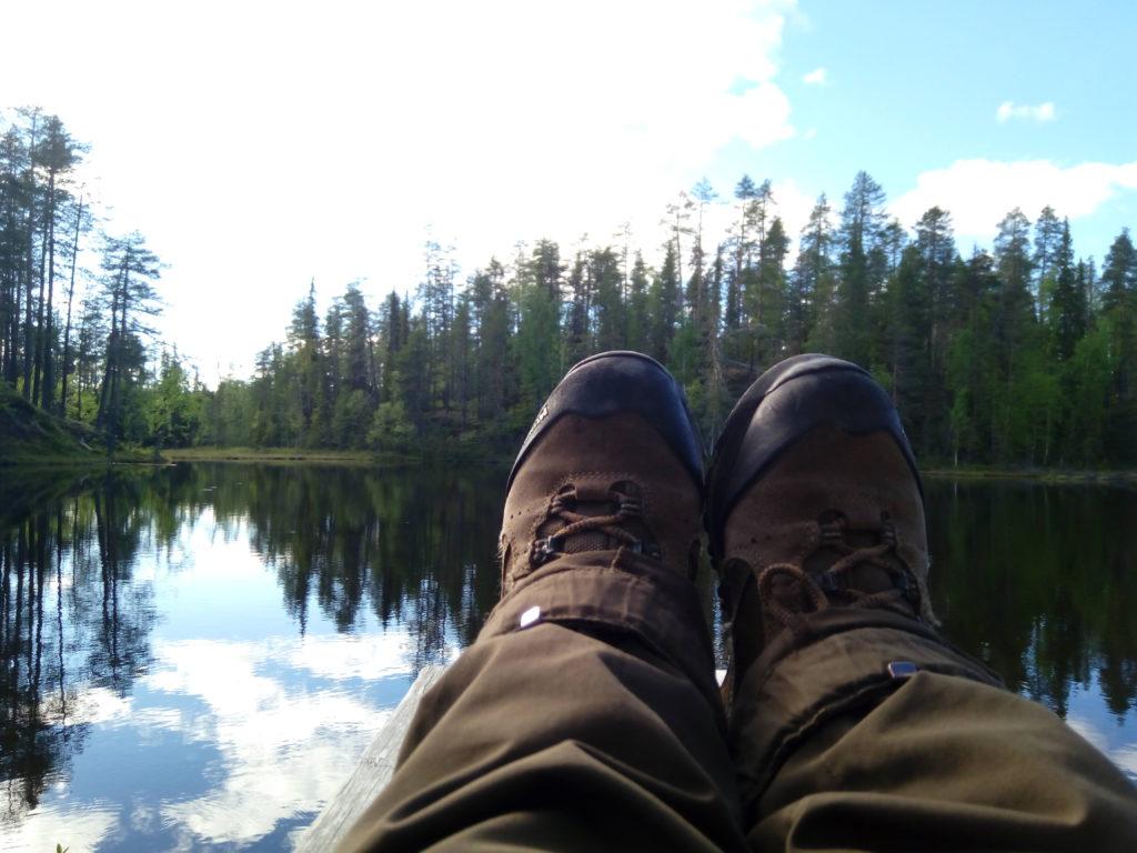 Vaelluskenkien peittämät jalat laiturilla lammen yllä. Valkoiset pilvet ja sininen taivas heijastuvat lammen pintaan.