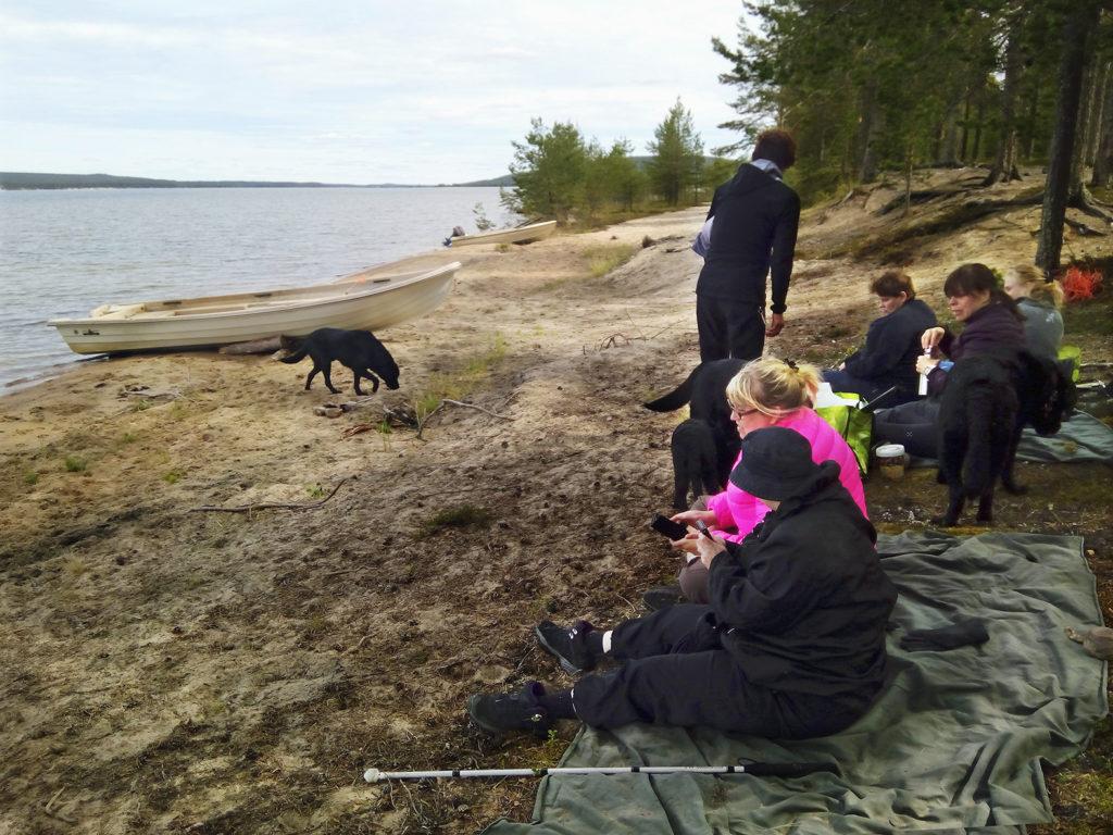 Seikkailijat värjöttelemässä hiekkarannalla vilttien päällä koirien nauttiessa vapaudesta ja vedestä.