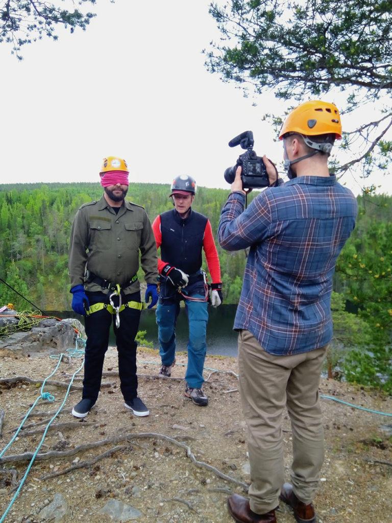 Mikko Halvari kuvaa Petri Markkasta joka huivi silmillään odottaa jyrkänteen reunalla omaa laskeutumisvuoroaan. Petrin takana on Jussi Tupasela.