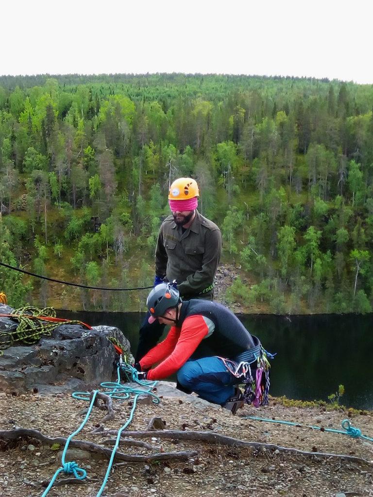 Jussi Tupasela varmistaa vielä Petri Markkasen kiinnitysköydet ennen laskua. Miehet ovat aivan jyrkänteen reunalla. Taustalla puiden peittämä vaara sekä sen edessä oleva vesistö.