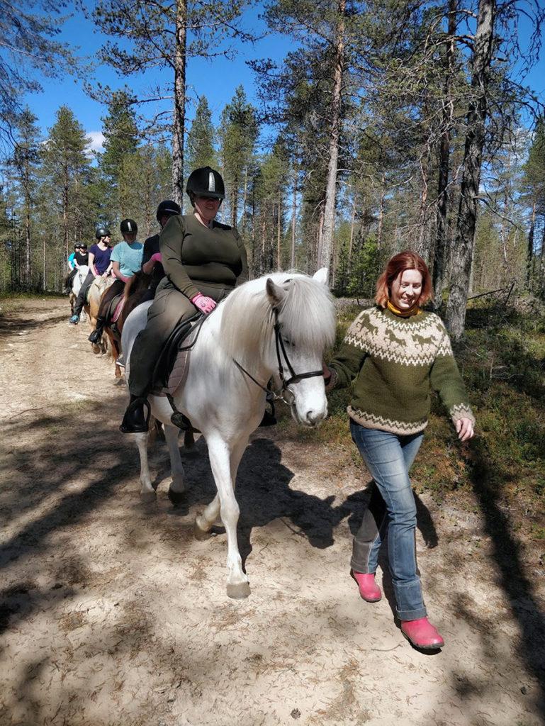 Seikkailijaryhmä ratsailla kauniissa aurinkoisessa kesäsäässä. Matka käy metsäautotietä letkassa Mirvan taluttaessa etummaisena kulkevaa Heidin hevosta.