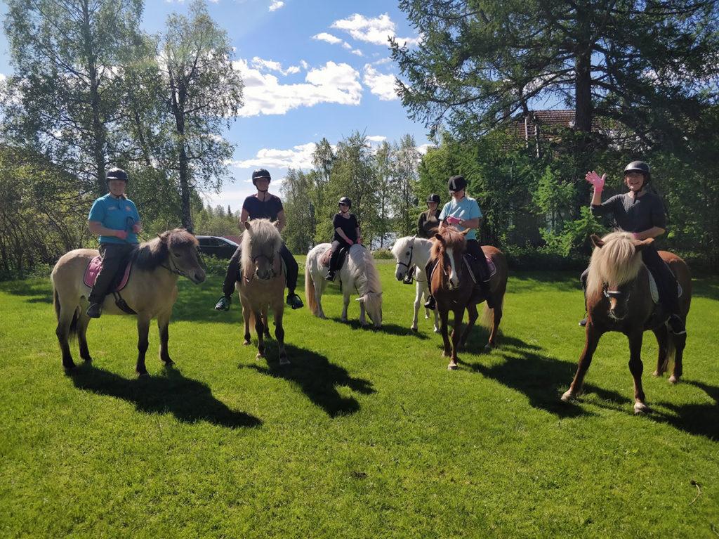 Yhteiskuva ryhmästämme ratsailla vihreällä ruohikolla. Hevoset eivät aivan malttaneet asettua riviin kuvaa varten. Aurinko paistaa. Taivaalla muutama poutapilvi.