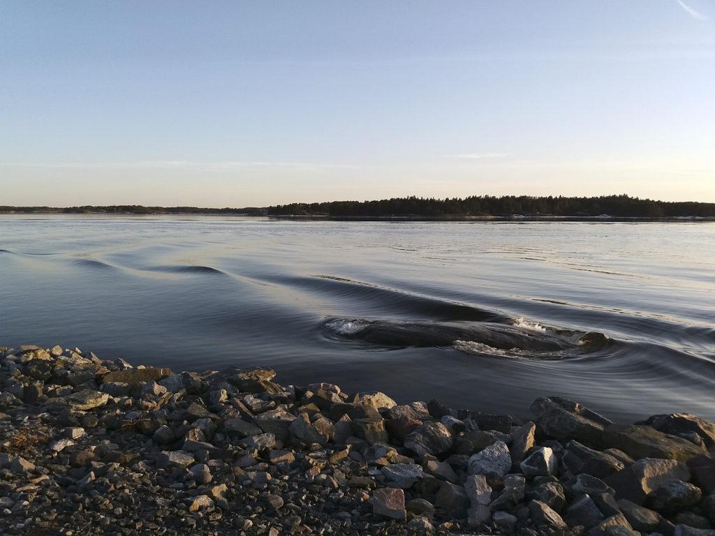 Alkavan illan viistossa lempeässä valossa aallon soljuva viiva lähestyy rannan kivikkoa. Horisontista nousee illan pastellinvärinen auer taivaan sineen.