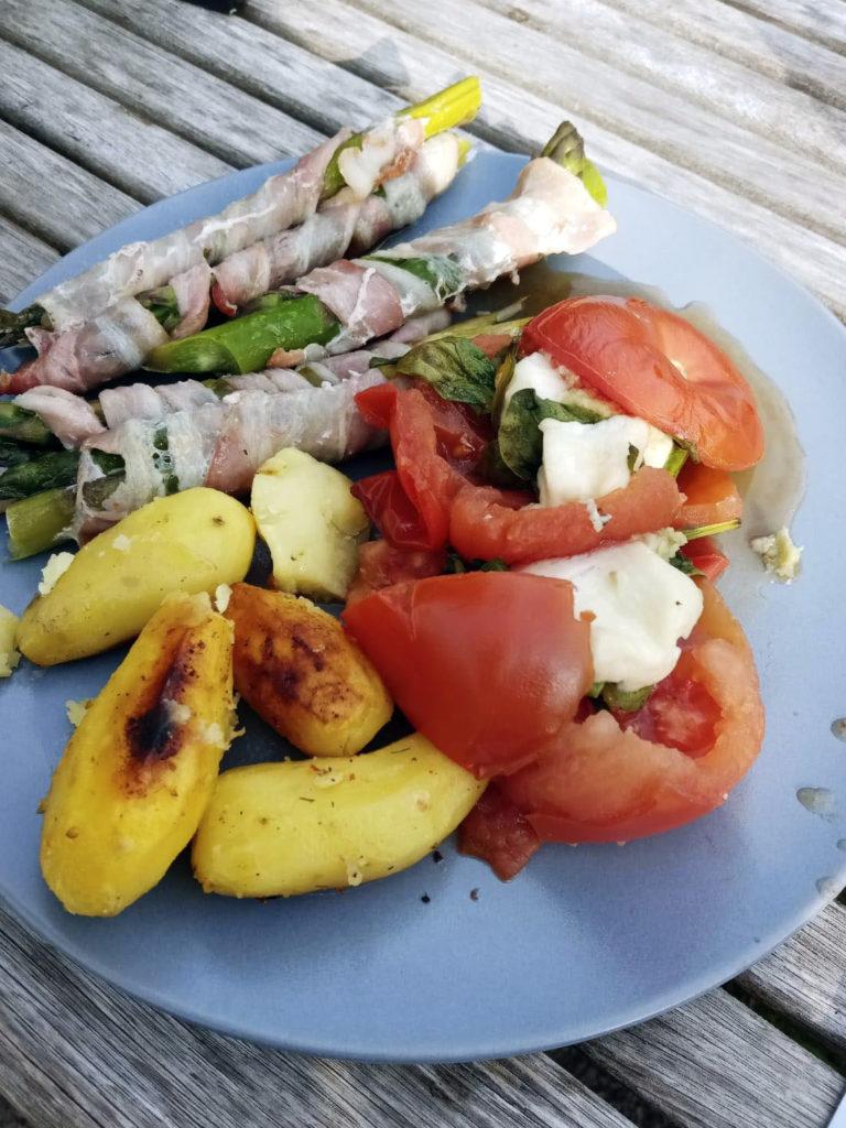 Herkullinen grilliateria lautasella: pekoniin käärittyjä parsoja, täytettyjä tomaatteja ja puikulaperunoita.