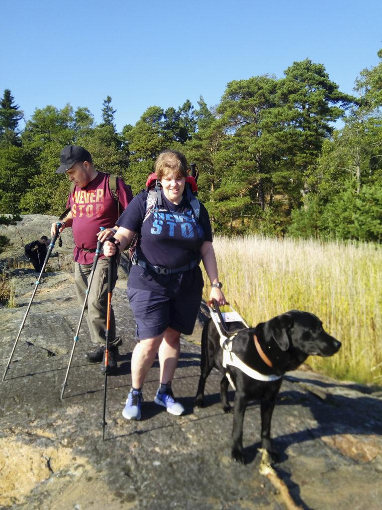 Heidi, Rauno ja Otto retkellä Pihlajasaaren kallioisissa maisemissa kauniina syyskesän päivänä. Taivas on sininen ja t-paidassa tarkenee.